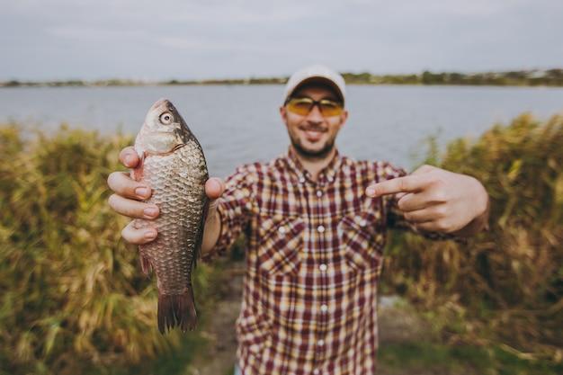 바둑판 무늬 셔츠, 모자, 선글라스를 끼고 면도하지 않은 젊은 남자가 물고기를 잡고 그것을 보여주고 물과 갈대의 배경에 있는 호수 기슭에 손가락으로 가리킵니다. 라이프 스타일, 어부의 레저 개념