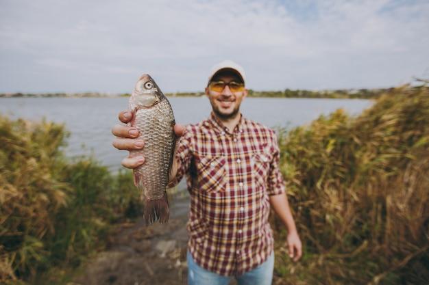 바둑판 무늬 셔츠, 모자, 선글라스를 끼고 면도하지 않은 젊은 남자가 물고기를 잡고 물, 관목, 갈대를 배경으로 호수 기슭에서 그것을 보여주고 미소를 짓습니다. 라이프 스타일, 어부의 레크리에이션, 레저 개념