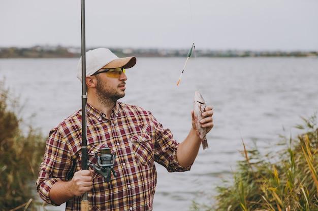 바둑판 무늬 셔츠, 모자, 선글라스를 끼고 면도하지 않은 젊은 남자가 낚싯대를 꺼내고 관목과 갈대 근처의 호숫가에서 잡은 물고기를 안고 있습니다. 라이프 스타일, 레크리에이션, 어부의 레저 개념