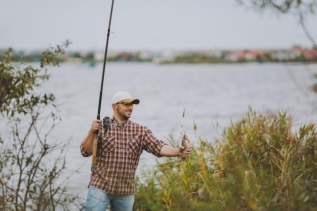 바둑판 무늬의 셔츠, 모자, 선글라스를 쓴 면도를 하지 않은 젊은이는 잡은 물고기가 있는 낚싯대를 꺼내고 관목과 갈대 근처의 호숫가에서 기뻐합니다. 라이프 스타일, 레크리에이션, 어부의 레저 개념
