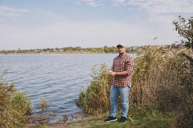 바둑판 무늬 셔츠, 모자, 선글라스를 끼고 면도하지 않은 젊은 남자가 호수 옆에 서서 물, 관목, 갈대 배경에 구더기가 든 작은 상자를 들고 있습니다. 라이프 스타일, 어부의 레크리에이션, 레저 개념