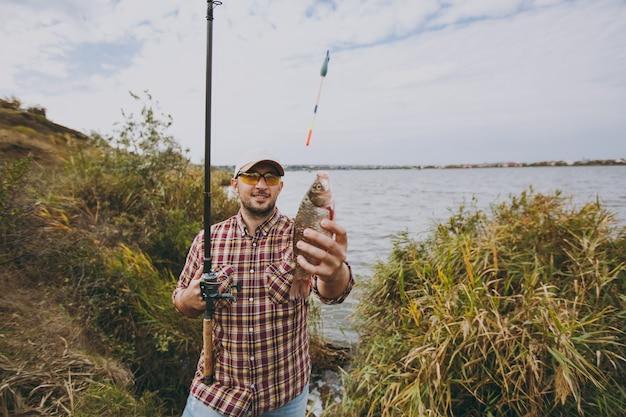 면도하지 않은 젊은 남자는 체크무늬 셔츠, 모자, 선글라스를 끼고 낚싯대를 들고 관목과 갈대 근처의 호숫가에서 잡은 물고기를 향해 손을 뻗습니다. 라이프 스타일, 레크리에이션, 어부의 레저 개념
