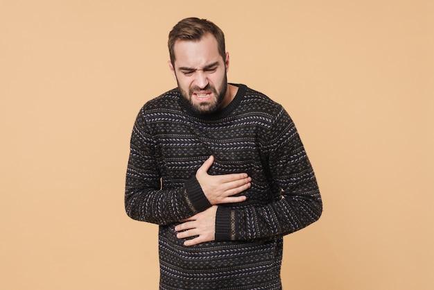 Молодой небритый мужчина в зимнем свитере касается своего живота из-за боли, изолированной над бежевой стеной