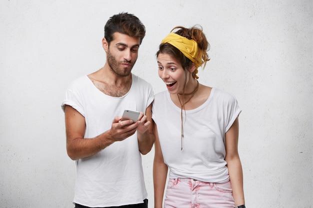 Giovane uomo con la barba lunga in maglietta bianca che tiene smartphone mostrando qualcosa sul telefono cellulare a sua moglie. giovane femmina sorpresa che osserva con gli occhi in pieno di incredulità nello smartphone di suo marito