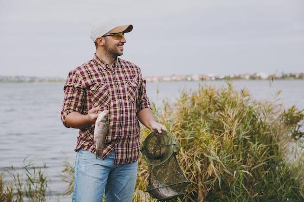 Il giovane uomo sorridente con la barba lunga in camicia a scacchi, berretto, occhiali da sole che guarda lontano tiene in mano una griglia da pesca verde e pesce che ha catturato sulla riva del lago vicino a canne. stile di vita, concetto di svago del pescatore