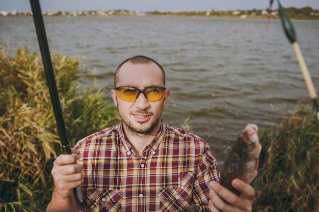 바둑판 무늬 셔츠와 선글라스를 끼고 면도를 하지 않은 젊은 남자는 낚싯대를 꺼내고 관목과 갈대 근처의 호숫가에서 잡은 물고기를 안고 있습니다. 라이프 스타일, 레크리에이션, 어부의 레저 개념