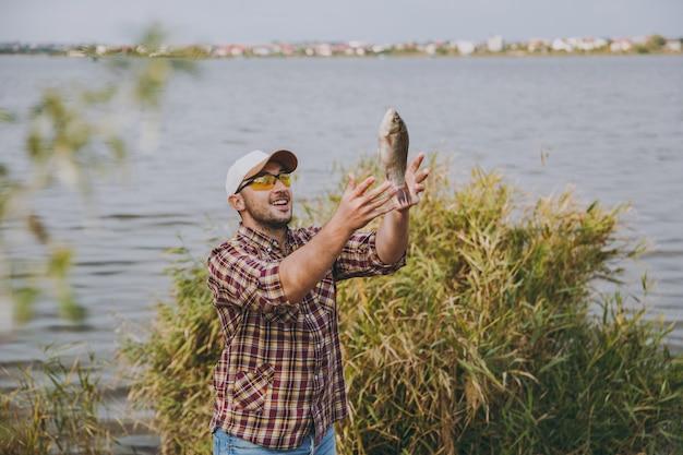 바둑판 무늬 셔츠, 모자, 선글라스를 끼고 면도를 하지 않은 젊은 남자가 물고기를 잡아 물, 관목, 갈대를 배경으로 호수 기슭에 던졌습니다. 라이프 스타일, 레크리에이션, 어부의 레저 개념
