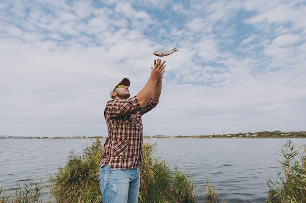 市松模様のシャツ、帽子、サングラスを身に着けた若い無精ひげを生やした笑顔の男が魚を捕まえ、水、低木、葦を背景に湖の岸に投げます。ライフスタイル、レクリエーション、漁師のレジャーの概念