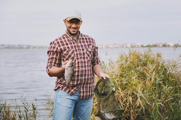 市松模様のシャツ、帽子、サングラスを身に着けた若い無精ひげを生やした笑顔の男は、低木や葦の近くの湖の岸で捕まえた緑の釣りグリッドと魚を手にしています。ライフスタイル、漁師のレジャーの概念