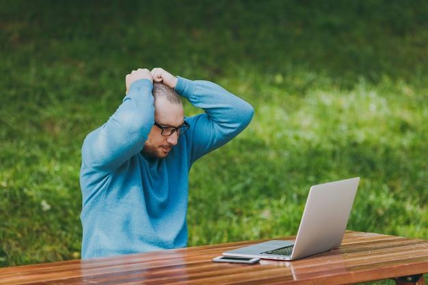 カジュアルな青いシャツを着た若い動揺した怒っているショックを受けた男性のビジネスマンや学生、眼鏡は都市公園のテーブルに座って屋外でラップトップの仕事を使用して問題を心配して頭に手を置きます。モバイルオフィスのコンセプト。