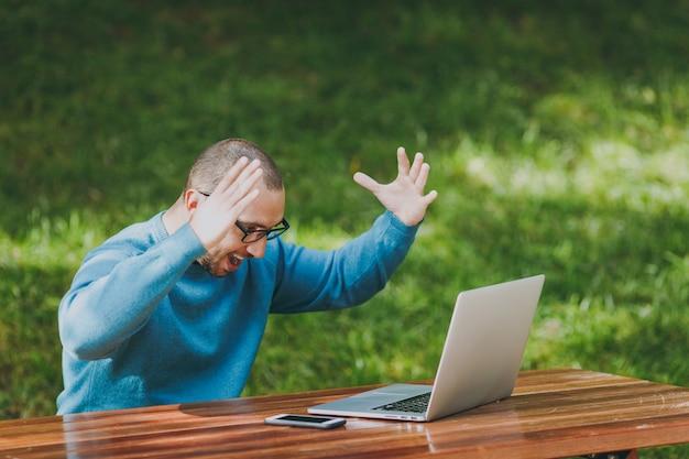 Молодой расстроенный сердитый шокированный человек, бизнесмен или студент в повседневных голубых очках, сидящих за столом в городском парке, используют ноутбук, работающий на открытом воздухе, вскидывают руки, обеспокоенные проблемами концепция мобильного офиса.