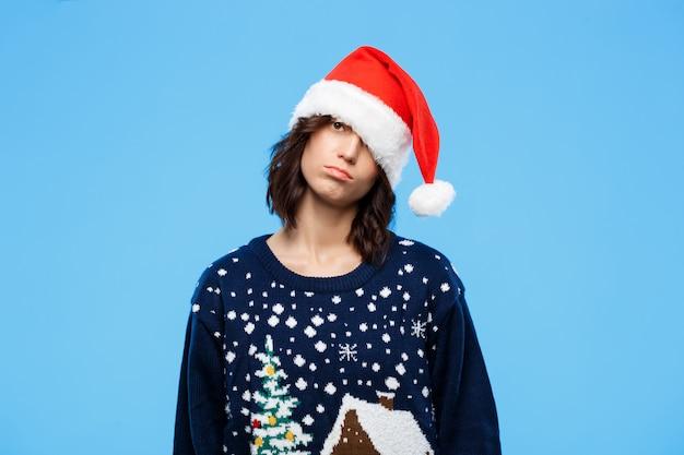 Молодая расстроенная красивая брюнетка в вязаном свитере и новогодней шапке над синей стеной