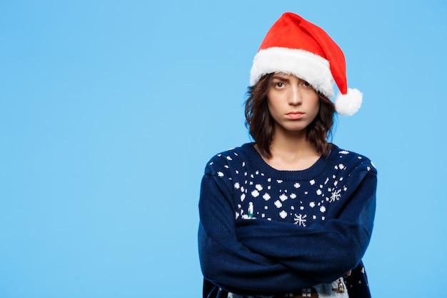 파란색 벽 위에 니트 스웨터와 크리스마스 모자에 젊은 화가 아름다운 갈색 머리 소녀