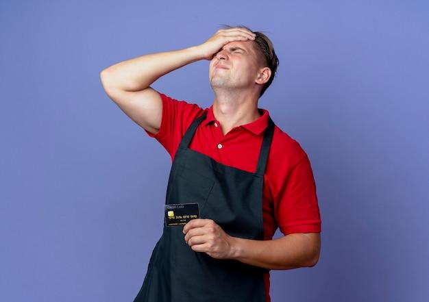 制服を着た若い動揺金髪男性床屋は、クレジットカードを保持している頭に手を置きます