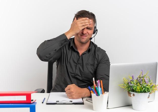 Giovane bionda sconvolto lavoratore di ufficio uomo sulle cuffie si siede alla scrivania con strumenti per ufficio utilizzando il computer portatile mette la mano sulla testa isolata su sfondo bianco con spazio di copia