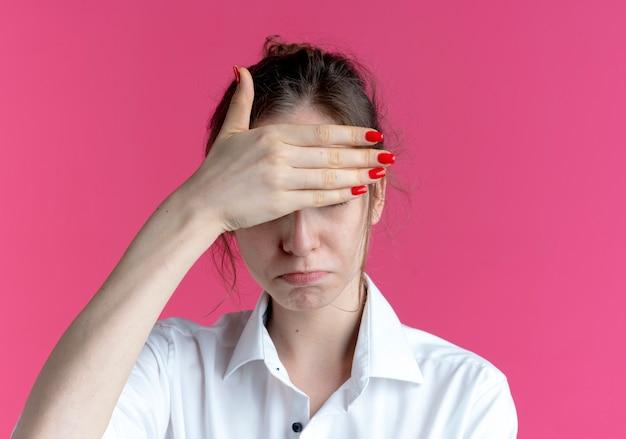 젊은 화가 금발 러시아 여자 복사 공간이 분홍색 공간에 고립 된 손으로 눈을 숨 깁니다