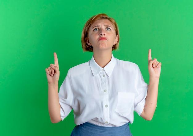 La giovane ragazza russa bionda sconvolta indica isolato su sfondo verde con spazio di copia