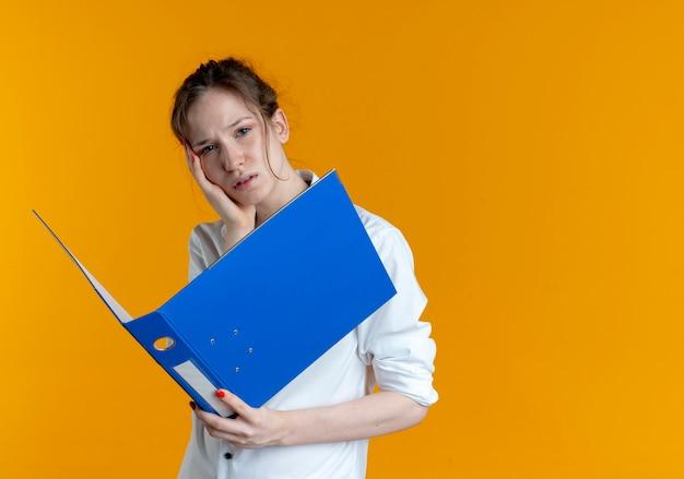 La giovane ragazza russa bionda sconvolta mette la mano sul mento che tiene la cartella di file isolata sullo spazio arancione con lo spazio della copia