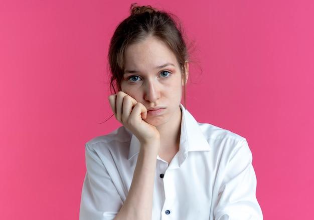 La giovane ragazza russa bionda sconvolta mette la mano sul mento che guarda l'obbiettivo sul rosa con lo spazio della copia