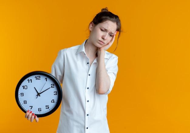 La giovane ragazza russa bionda sconvolta mette la mano sulla faccia che tiene l'orologio isolato sullo spazio arancione con lo spazio della copia