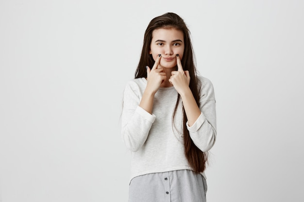Young upset brunette female teenage making fake smile with her fingers stretching the corners of her mouth. portrait of woman trying to stay positive