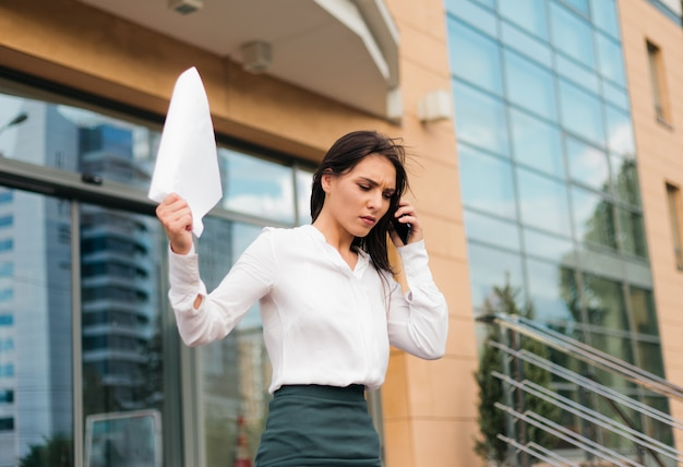 Young upset business woman is wearing blouse and a skirt leaving the business center and going down the stairs