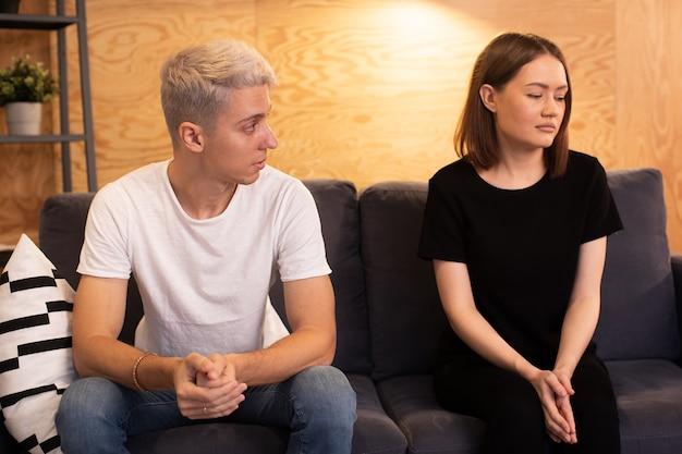 若い動揺したカップルは心理学者と一緒に座っています。若いカップルは動揺しています