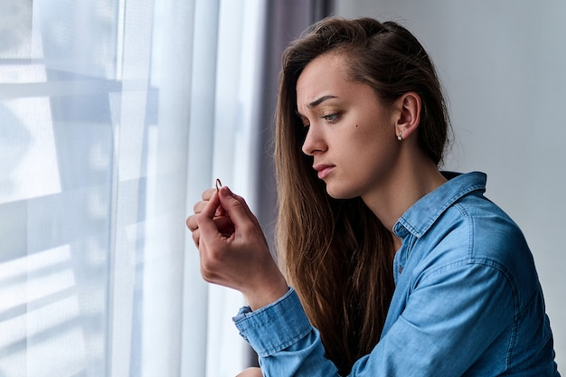 Young upset depressed lonely divorced woman with sad eyes in a shirt holds gold ring and sits alone at home during worrying about failed marriage after break up relationship and divorce