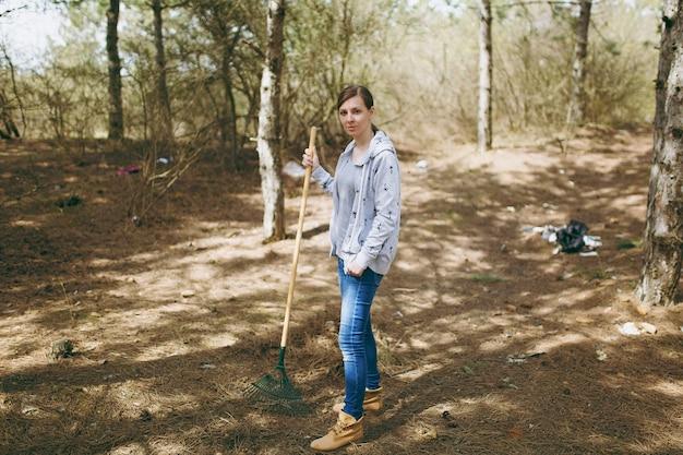 지저분한 공원에서 쓰레기 수거를 위해 갈퀴를 사용하여 평상복을 입고 청소하는 젊은 화난 지친 여성