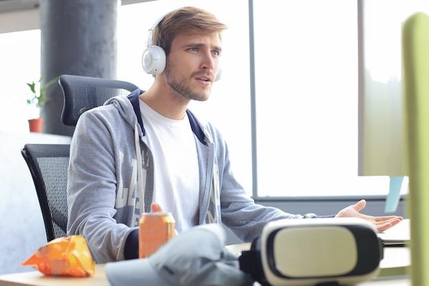 コンピューターでオンラインビデオゲームをプレイしている若い動揺ゲーマーは落ち込んでいます。