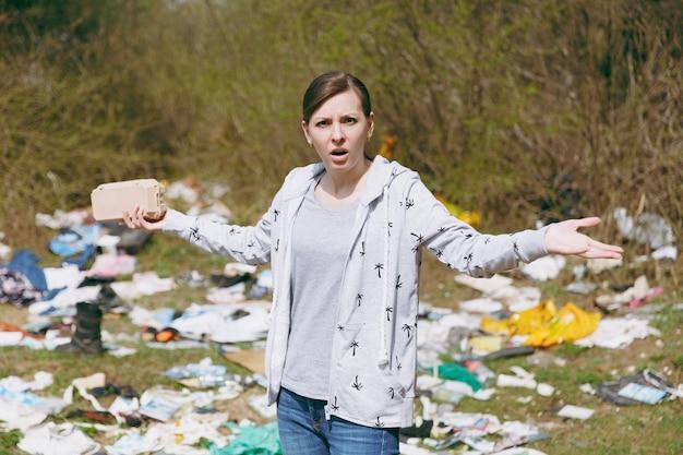 Молодая расстроенная раздраженная женщина в уборке повседневной одежды, держащая мусор и разводящая руки в замусоренном парке. проблема загрязнения окружающей среды. остановить мусор природы, концепция защиты окружающей среды.