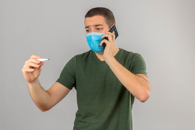 Young  upset looking man in medical mask looking at digital thermometer and speaking by smartphon isolated on white