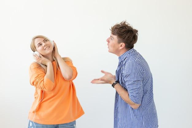 若い動揺した男は彼の女性に彼の話を聞くように頼みますが、彼女は白い壁にポーズをとっているヘッドフォンで音楽を聴いています。誤解と対話への不本意。