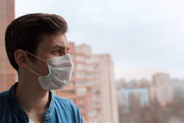 Covid-19 격리로 인해 격리 된 집에 머무르는 의료 마스크의 젊은 화가 남자