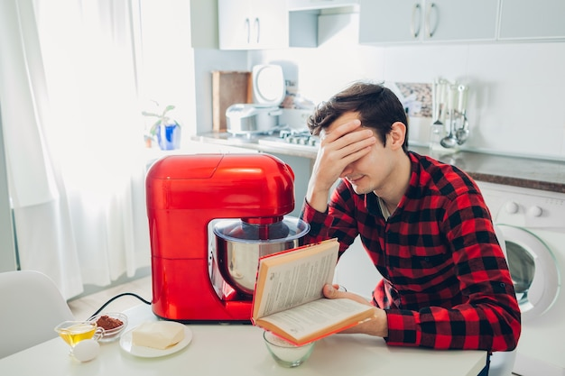 Young upset man reading complicated recipe in culinary book at home. guy cooking pie with food processor on kitchen.
