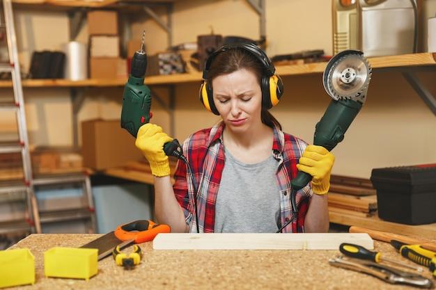 格子縞のシャツ、灰色のtシャツ、遮音性のヘッドフォン、さまざまなツール、電動のこぎり、電気ドリルを使って木製のテーブルの場所で大工のワークショップで働いている黄色い手袋を着た若い動揺した悲しい女性。