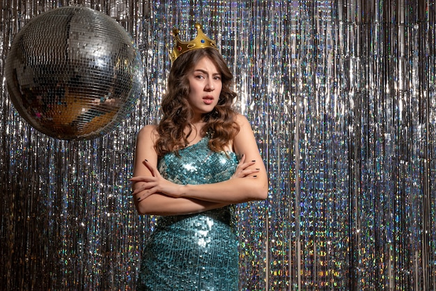 파티에서 왕관과 함께 장식 조각과 푸른 녹색 반짝이 드레스를 입고 젊은 화가 불행한 매력적인 아가씨