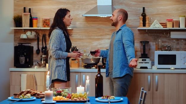 낭만적인 저녁 식사를 하는 동안 남편과 싸우는 화가 난 젊은 아내. 갈등이 있는 불행한 성인 부부는 부엌에서 말다툼을 하는 데 어려움을 겪고 있습니다.