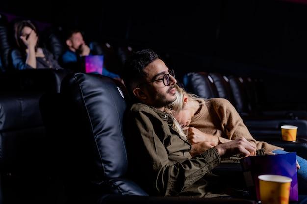 Молодая расстроенная женщина плачет на плече своего парня, сидя в креслах перед большим экраном в кинотеатре
