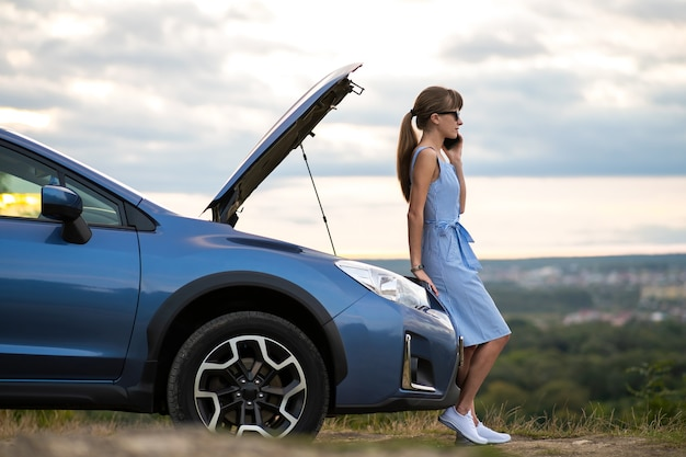Young upset woman driver talking on mobile phone near a broken car with open hood inspecting engine having trouble with her vehicle.