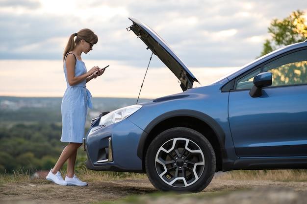 Молодой расстроенный водитель женщины разговаривает по мобильному телефону возле разбитой машины с открытым капотом, осматривая двигатель, имеющий проблемы с ее транспортным средством.