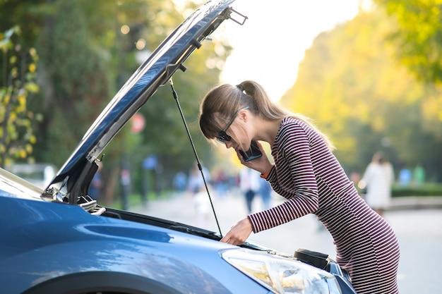 Молодая женщина-водитель расстроена разговаривает по мобильному телефону возле разбитой машины с открытым капотом, ожидая помощи, имея проблемы с ее автомобилем на городской улице.