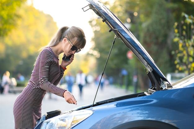 Молодая расстроенная женщина-водитель разговаривает по мобильному телефону возле разбитой машины с открытым капотом в ожидании помощи, у нее проблемы с автомобилем на городской улице