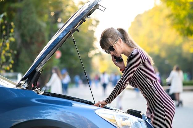 Молодая расстроенная женщина-водитель разговаривает по мобильному телефону возле разбитой машины с открытым капотом, ожидая помощи, имея проблемы с ее автомобилем на городской улице.