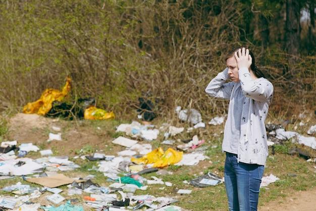 Молодая женщина расстроена в уборке повседневной одежды, цепляясь за голову, глядя на кучу мусора в замусоренном парке. проблема загрязнения окружающей среды. остановить мусор природы, концепция защиты окружающей среды.