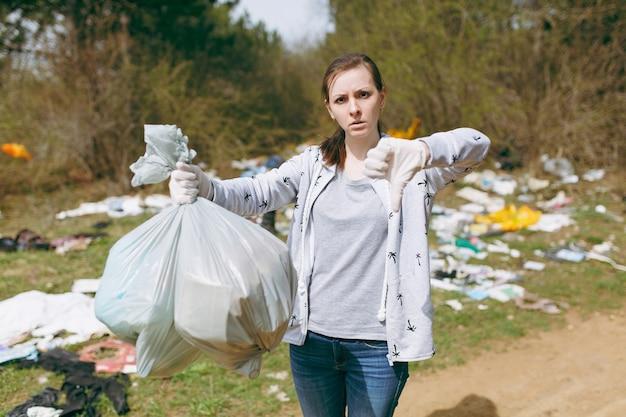 Молодая женщина расстроена в уборке повседневной одежды, держа мешки для мусора и показывая большой палец вниз в замусоренном парке. проблема загрязнения окружающей среды. остановить мусор природы, концепция защиты окружающей среды.