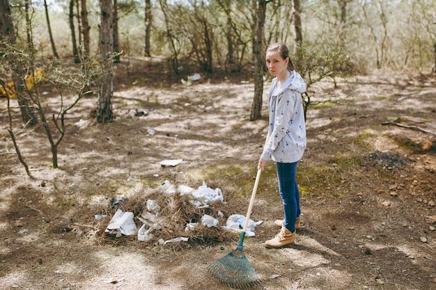 흩어진 공원에서 쓰레기 수거를 위해 갈퀴를 사용하여 쓰레기를 청소하는 캐주얼 옷을 입은 젊은 화가 여성. 환경오염 문제