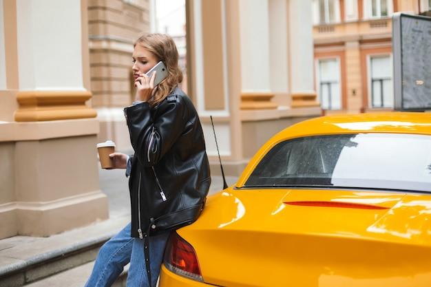 街の通りで悲しいことに携帯電話で話している間黄色のスポーツカーに寄りかかって行くコーヒーのカップと革のジャケットの若い動揺した女性