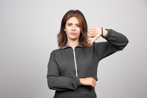 Молодая женщина расстроена показывает палец вниз на серой стене.
