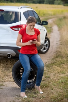 Young upset woman siting on spare tire next to broken car at field and searching for service phone number